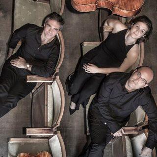 Foto en plan cenital, visto desde arriba de los tres integrantes del Trío Pangea sentados en el patio de butacas mirando a cámara, o sea hacia arriba, con su violín y su chelo al lado