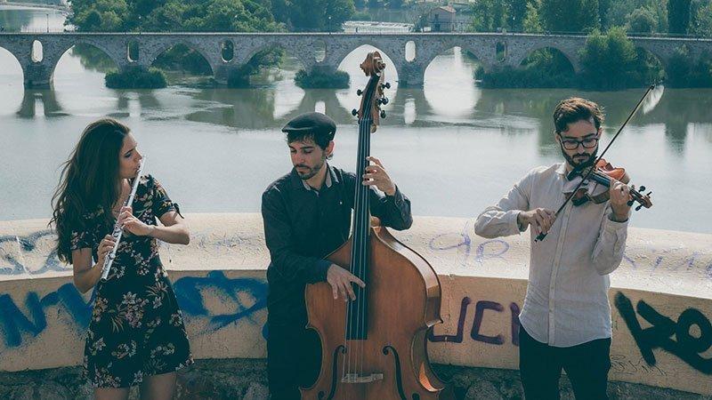 Foto de los tres miembros de Vandalia Trío tocando sus instrumentos en un balcón frente al rio, con un puente romano de fondo