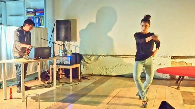 Foto de Ana Arenas bailando en directo con un músico a los mandos del sistema de sonido