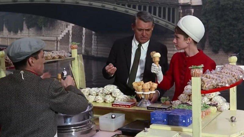 Fotograma de la película Charade en el que se ve a Cary Grant y Audrey Hepburn comprando un helado en un puesto ambulante