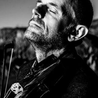 Foto promocional de Duncan Chisholm en la que se le ve en primer plano tocando el violín con los ojos cerrados y cara de gloria bendita