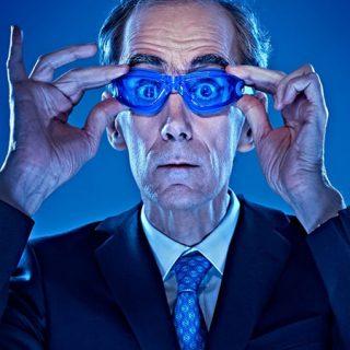 Foto del personaje principal sobre fondo azul sosteniendo en su cara unas gafas de buceo de color azul