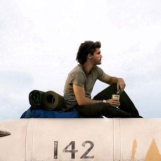 Detalle del cartel de la película en el que se ve al protagonista sentado sobre el autobus que le sirve de cobijo durante parte de su aventura