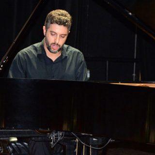 Foto de Javier Negrín tocando un piano de cola con cara de máxima concentración y esmero