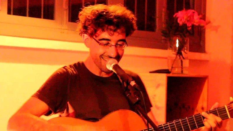 Foto de La Baldosa Flotante tocando la guitarra y cantando en uno de sus conciertos