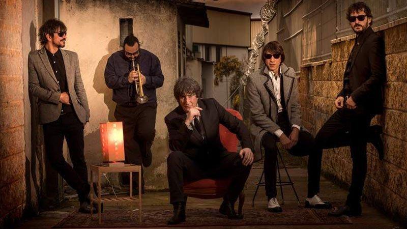 Foto de los cinco integrantes de Pájaro posando en un callejón con su frontman Andrés Herrera en el centro sentado en una butaca con pose chulesca