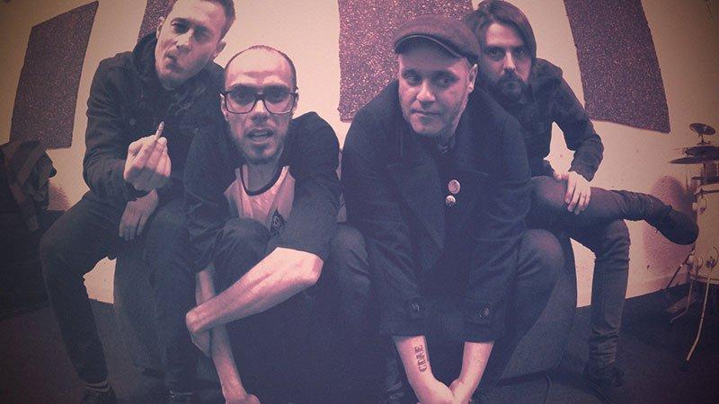Foto de los cuatro miembros de Thee Operators posando sentados en un sofá