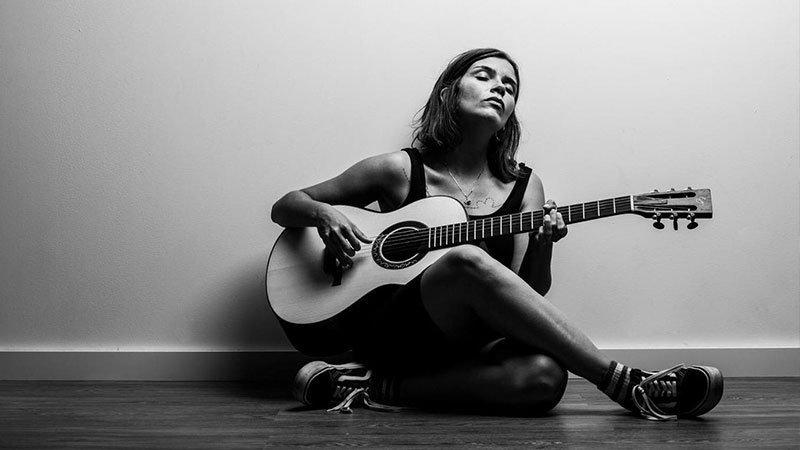 Foto en blanco y negro de Carmen Boza sentada en el suelo tocando una guitarra acústica con los ojos cerrados y cara de gran sentimiento