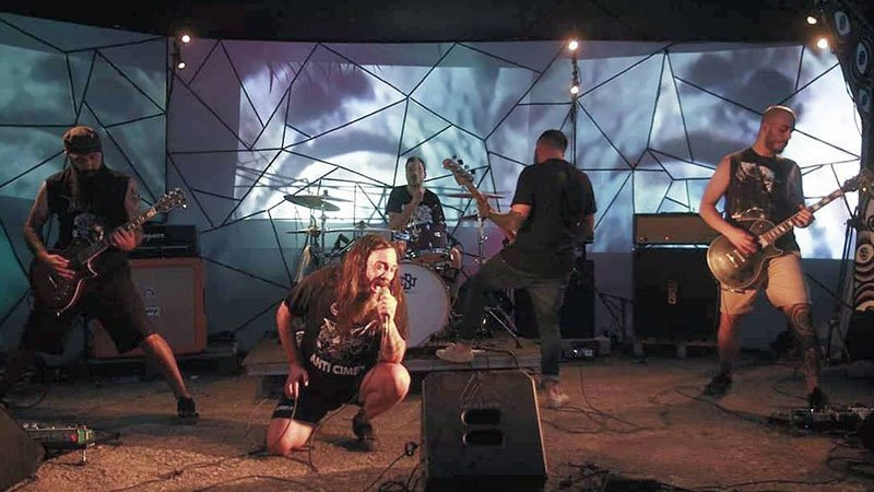 Foto de Dumange tocando en directo, donde se ve a los 5 miembros repartidos por un escenario con visuales de fondo
