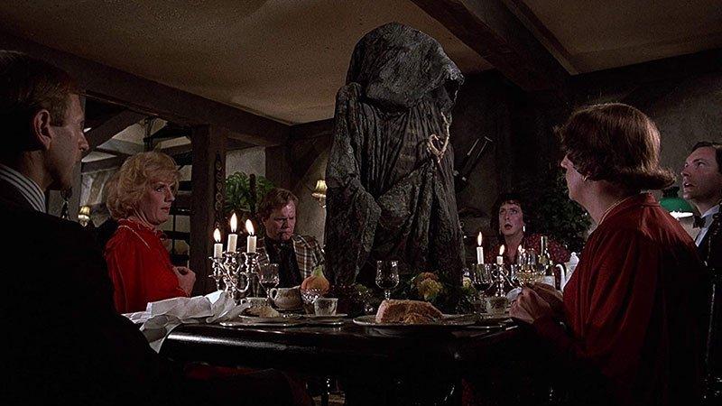 """Fotograma de la película """"El sentido de la vida"""" en el que se ve a una gente sentada a la mesa para la cena, con candelabros y todo muy bien puesto, ante ellos se muestra una gran silueta negra que representa la muerte"""