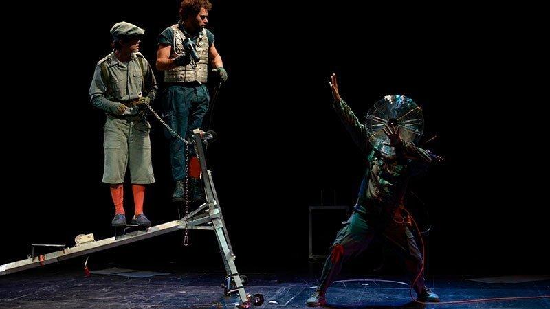 """Fotografía de una escena de la obra """"El viaje de Ulises"""" en la que se ve a dos personajes subidos a un poste caído a la izquierda del plano mientras un tercero, a la derecha del plano hace gestos con las manos con una esfera transparente en su cabeza a modo de casco galáctico sideral"""