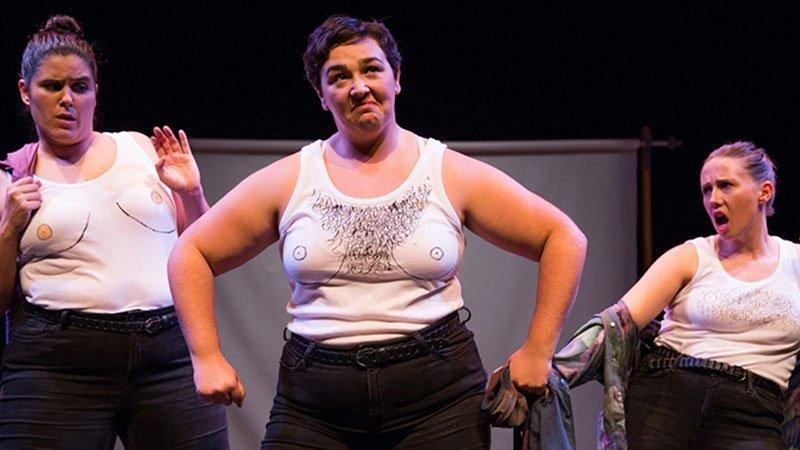 """Foto de una escena de la obra """"Elisa y Marcela"""" en la que se ve a las tres actrices, en el centro una de ellas imita la actitud de un macho garrulo estándar"""