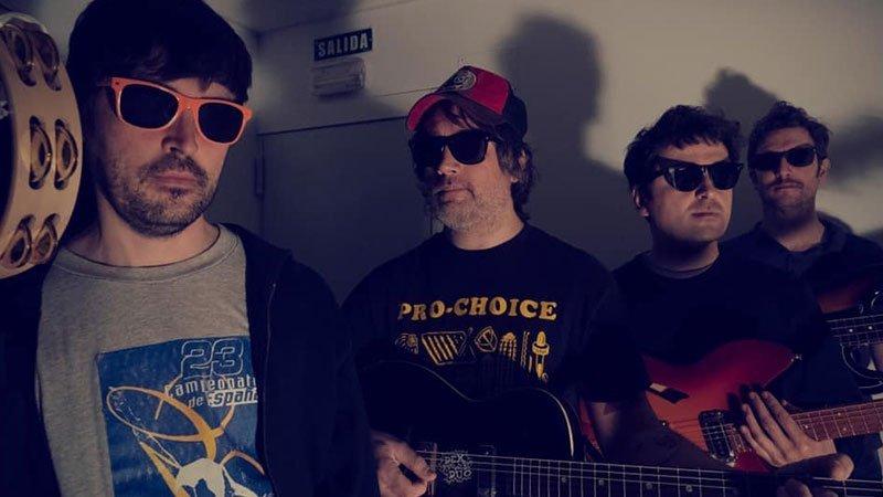 Foto de los cuatro componentes de Exnovios con sus instrumentos en la mano, gafas de sol y posición comico-desafiante