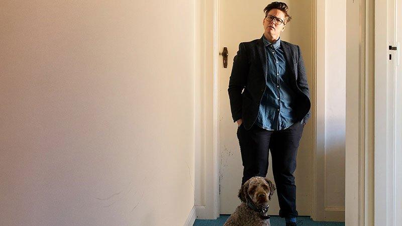 Foto de Hannah Gadsby en el pasillo de su casa mirando a cámara con gesto increpante, delante de ella se ve a su perro también mirando a cámara