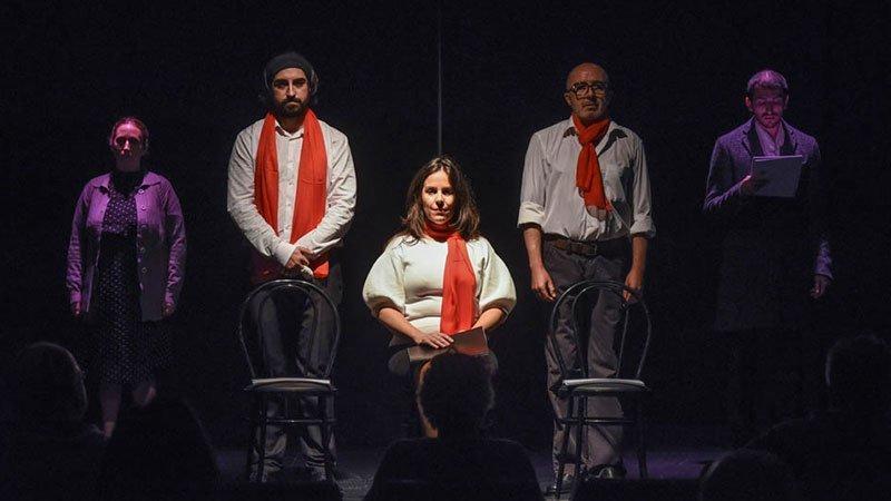Foto de una escena de la obra en la que aparecen 5 personajes, cuatro de ellos en pie, firmes y en paralelo, y en el centro una quinta personaje sentada e una silla y con una soga al cuello