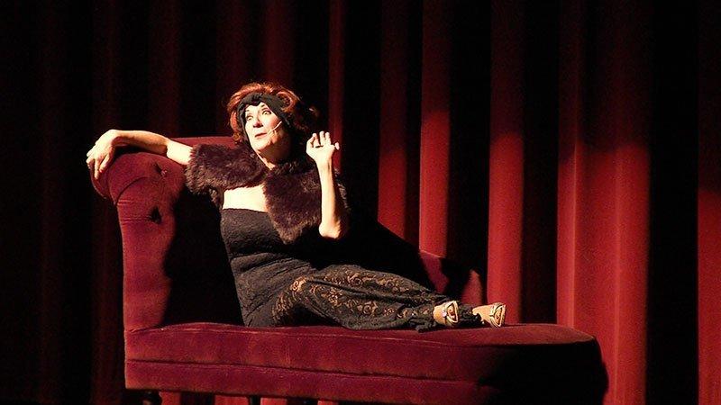 Fotografía de una escena de la obra en la que se ve a la protagonista recostada sobre un diván hablando con gesto glamuroso y gesto socarrón