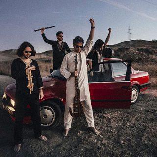 Foto de los cuatro componentes de Mohama Saz en un exterior árido al anochecer, vestidos con atuendo arabesco, de pie alrededor de un coche rojo, alzadando una mano con el puño cerrado y sosteniendo algunos de sus instrumentos