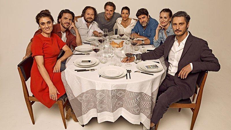 """Foto promocional de la obra """"Perfectos desconocidos"""" en la que se ve a todo el reparto de actores sentados alredador de una mesa"""