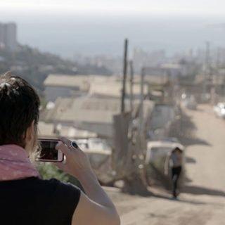 """Fotograma del documental """"Push"""" en el que se ve a Leilani Farha tomando una foto de un barrio marginal de Chile, se ve un panorama de chabolas y al fondo, a lo lejos, los enormes edificios de la ciudad"""