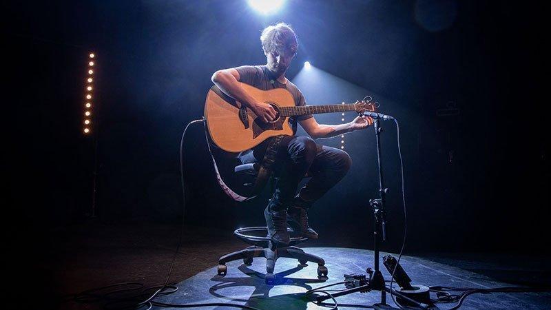 Foto de Reinis Jaunais en directo, sentado en una silla en el escenario abraza su guitarra y ajusta la tensión de las cuerdas en medio de un directo