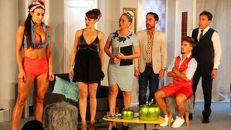 Fotografía de una escena de la obra en la que se ve a cinco de los personajes principales mirando acusativamente a una de los personajes en la izquierda del plano