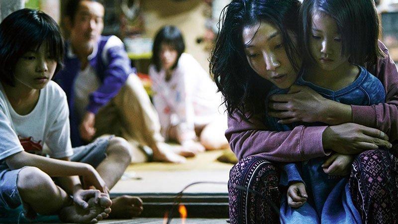 Fotograma de la película Manbiki kazoku en el que se ve a todos los miembros de la familia protagonista en un plano en el que a la derecha vemos a la madre cogiendo a uno de los niños y mirando sorprendidos a una llama, que está en la parte inferior central del plano, mientras el resto de personajes miran desde atrás.