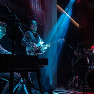 Foto de Vels Trio tocando en directo en un escenario con haces de luz azul a su alrededor