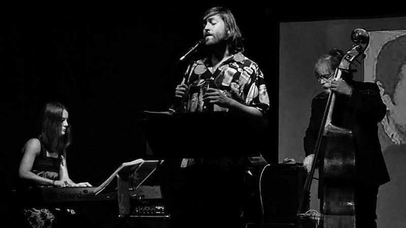 Foto en blanco y negro del grupo Bombara! tocando en directo donde se ve a tres de los miembros: piano (teclados) a la izquierda, voz en el centro y contrabajo a la derecha