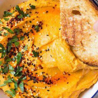 Foto de un bol de hummus de calabaza sobre una mesa con hierbas verdes por encima. En la foto una mano entra por la derecha del plano sosteniendo un trozo de pan tostado que hunde en el hummus.