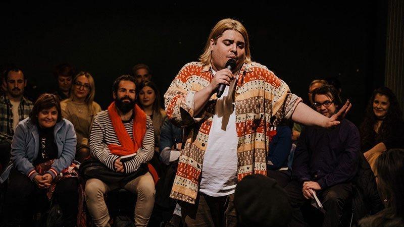 Foto de Duncan Macmillan en su show en directo, agarrando el micrófono con cara irónica y haciendo un gesto con la mano derecha muy simpático