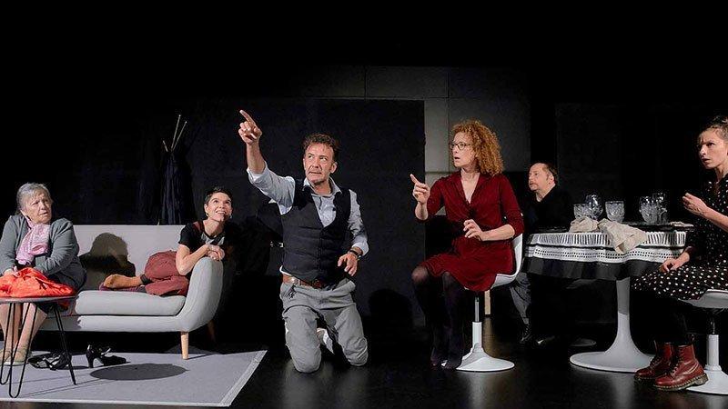 """Fotografía de una escena de la obra teatral """"El Mago"""" en la que se ve a todos sus protagonistas sentados, en el centro uno de ellos señala al cielo con gesto incriminatorio mientras el resto le miran asombrados"""