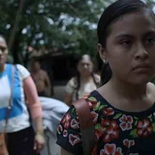 Fotograma de la película en el que se ve a la joven protagonista, Guie'dani, a la derecha el plano, con gesto de descontento, y a varios miembros de su familia al fondo mirándola