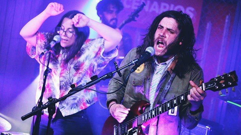 Foto de Fizzy Soup tocando en directo, donde se ve a la derecha a Javi, guitarra y voz, y al a izquierda a Sonia, voz y percusión, ambos con gesto y postura enérgicos y de gran pasión. De fondo se ve al bajista tocando.