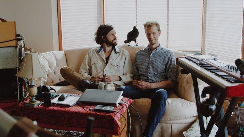 Foto de los dos integrantes de Green Hills Alone sentados en un sofá rodeados de instrumentos y un pájaro de porcelana.
