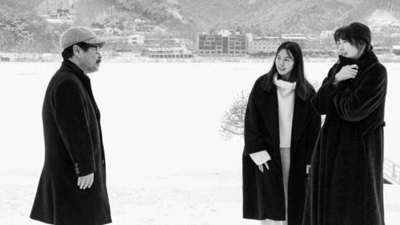Fotograma de la película Hotel by the river (Gangbyeon hotel) en el que se ve a sus tres personajes principales, el padre, a la izquierda del plano, mirando a sus dos hijas, a la derecha en un entorno nevado con unos edificios de fondo.