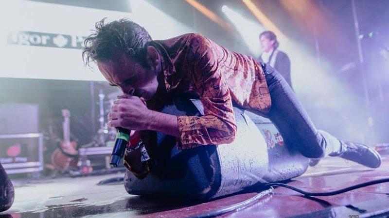 Foto de Igor Paskual en directo, tirado sobre una de las pantallas de sonido mientras canta agarrando fuertemente el micrófono