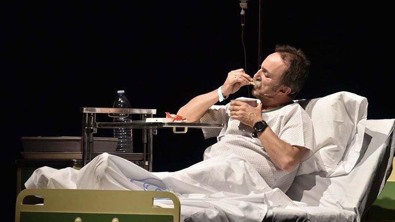"""Foto de una escena de la obra """"Infarto ¡No vayas a la luz!"""" en la que se ve a su protagonista sentado sobre una cama de hospital con su camisón de hospital y su gotero de hospital, la máscarilla de oxígeno subida a la frente y los ojos cerrados, con gesto meditativo"""