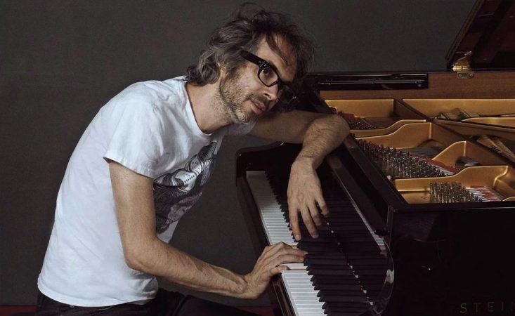 Foto de James Rhodes apoyado sobre un piano de cola como si estuviese cansado.