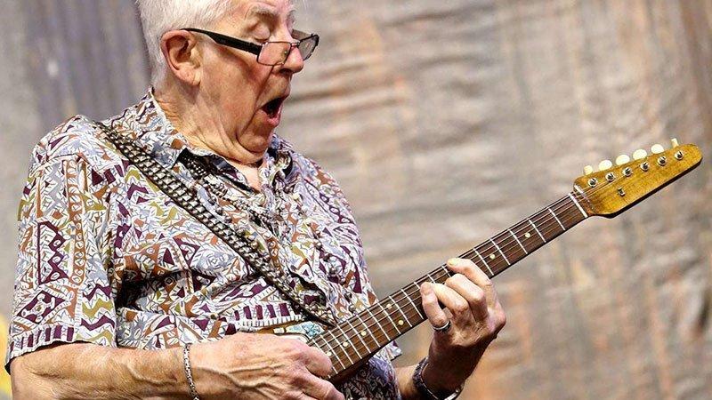 Foto de John Mayall tocando la guitarra en uno de sus directos, mirando hacia abajo con las gafas caídas hasta la punta de la nariz, la boca abierta y un gesto enérgico muy simpático