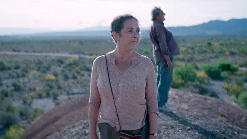 """Fotograma de la película """"La novia del desierto"""" en el que se ve a la protagonista en el centro, en primer plano de pie en un entorno de llanuras semidesérticas, al fondo, puede verse al co-protagonista de pie, desenfocado y de perfil."""