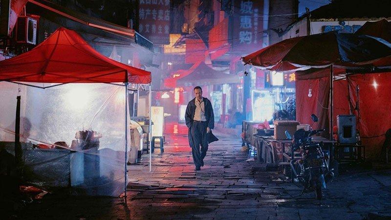 """Fotograma de la película """"Largo viaje hacia la noche"""" en el que se ve un precioso plano de una calle de china en perspectiva por la que camina hacia la cámara el protagonista con gesto desgarbado y las manos en los bolsillos."""