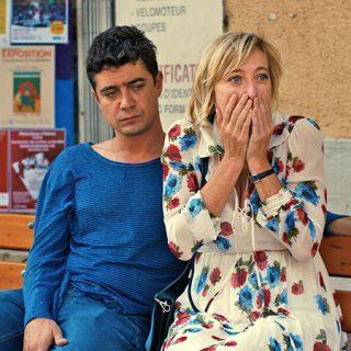 Fotograma de la película Les Estivants en laque se ve a la pareja protagonista sentados en un banco en la calle, él con gesto triste y ella sorprendida tapándose la boca con las manos