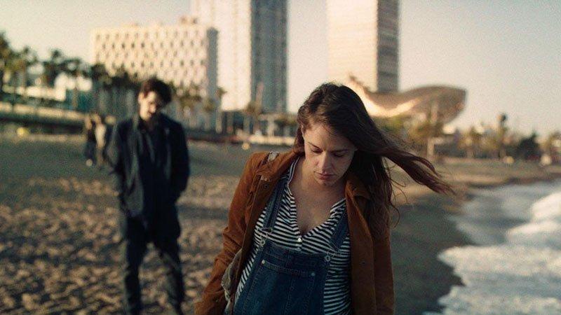 Fotograma de la película en el que se ve una escena en la playa de Barcelona, en primer plano se ve a la protagonista, con bombo de embarazada caminando por la orilla, de fondo, desenfocado, se ve al coprotagonista, mirándola parado con las manos en los bolsillos.