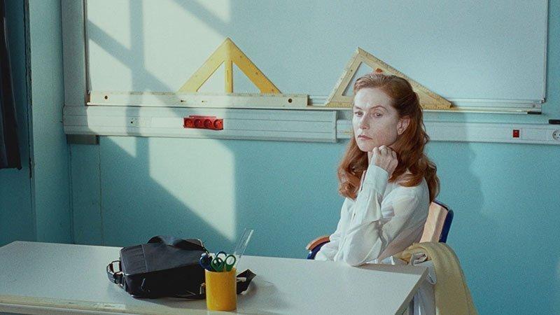 """Escena de la película """"Madame Hyde"""" en la que se ve a la protagonista sentada ante su mesa de profesora, con la pizarra al fondo."""