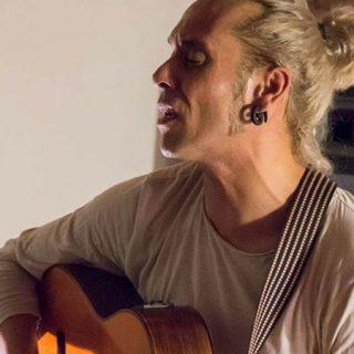 Foto de Moy Gomar tocando la guitarra y cantando en uno de sus directos.