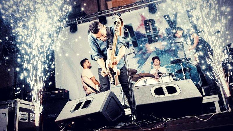 Foto de Nadye tocando en directo donde se ve al cantante y bajista esgrimiendo su instumento en primer plano y a los otros tres miembros de fondo