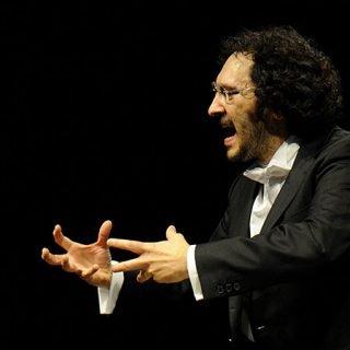 Foto de Nuno Côrte-Real en plena acción de dirección de orquesta, con un gesto de tensión en sus manos y de plena emoción en su rostro.