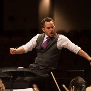 Foto de Andrew Grams en pleno concierto dirigiendo a una orquesta con gesto enérgico.