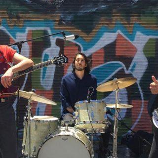 Foto de los tres integrantes de SadGirl en un directo en la calle, a pleno sol, con un graffiti de fondo, mirando a cámara y mostrando un gesto de manos con el puño cerrado y los pulgares extendidos, como queriendo decir que todo está OK.