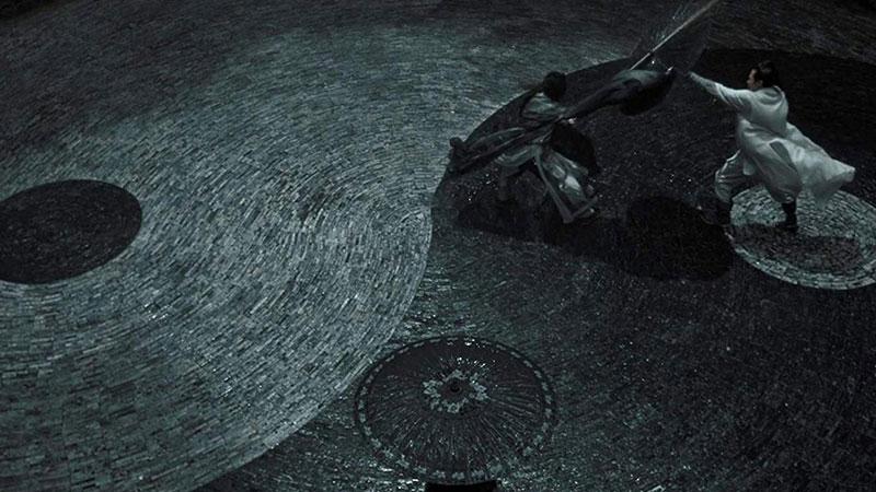 """Fotograma de """"Shadow"""" en el que se ve un plano inclinado superior de un terreno pintado como un ying yang en el que luchan dos personajes mientras una chica les mira"""